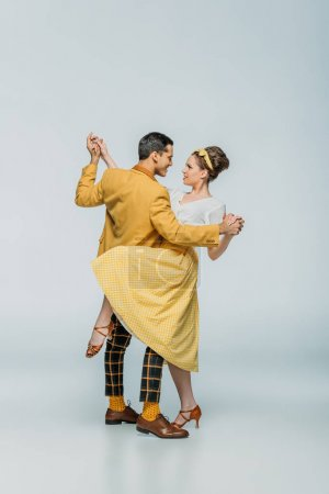 Photo pour Élégants danseurs tenant la main tout en dansant boogie-woogie sur fond gris - image libre de droit