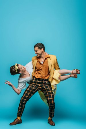 Photo for Handsome dancer holding girl while dancing boogie-woogie on blue background - Royalty Free Image