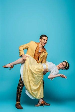 Photo pour Danseuse souriante soutien fille tout en dansant boogie-woogie sur fond bleu - image libre de droit