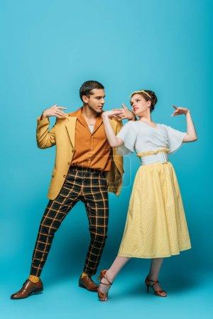 Photo pour Danseurs élégants qui se regardent tout en dansant boogie-woogie sur fond bleu - image libre de droit