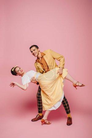 Photo pour Danseuse souriante soutien fille tout en dansant boogie-woogie sur fond rose - image libre de droit