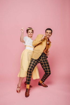 Photo for Cheerful dancers looking at camera while dancing boogie-woogie on pink background - Royalty Free Image