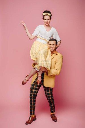 Photo pour Homme gai tenant une jolie fille en dansant boogie-woogie sur fond rose - image libre de droit