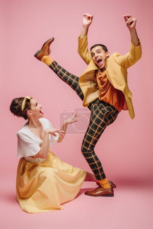 Photo pour Une jeune fille joyeuse assise sur le sol et un homme excité levant la jambe en dansant boogie-woogie sur fond rose - image libre de droit