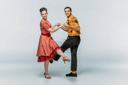 Photo pour Danseurs élégants regardant la caméra tout en dansant boogie-woogie sur fond gris - image libre de droit