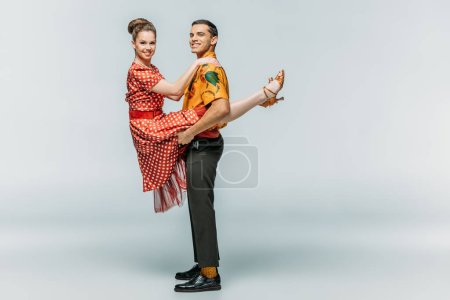 Photo for Cheerful man holding woman while dancing boogie-woogie on grey background - Royalty Free Image