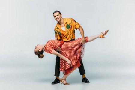 Photo pour Homme gai soutenir femme tout en dansant boogie-woogie sur fond gris - image libre de droit