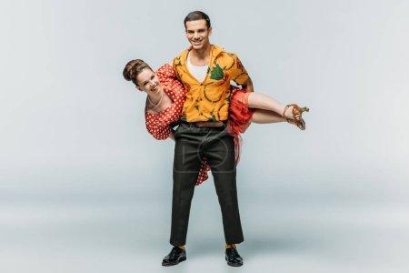Photo pour Homme gai tenant femme tout en dansant boogie-woogie sur fond gris - image libre de droit