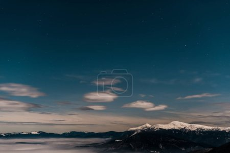 scenic view of snowy mountains with white fluffy clouds in evening