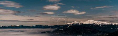 Photo pour Vue panoramique des montagnes enneigées avec des nuages blancs pelucheux en soirée, vue panoramique - image libre de droit