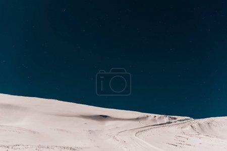 Photo pour Vue panoramique d'une montagne couverte de neige pure contre un ciel bleu foncé - image libre de droit