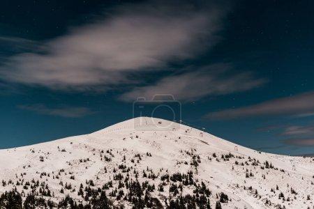 Photo pour Vue panoramique de la montagne couverte de neige et de pins sur ciel sombre en soirée - image libre de droit