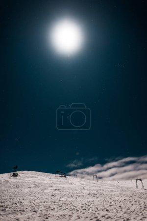 Photo pour Vue panoramique de la télécabine ascension dans une montagne couverte de neige contre un ciel sombre et un soleil brillant - image libre de droit