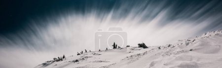 Photo for Scenic view of mountain covered with snow and pine trees against dark sky in evening with white cloud, panoramic shot - Royalty Free Image