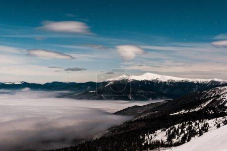 Foto de Vista panorámica de montañas nevadas con pinos y nubes blancas floridas en cielo oscuro por la noche. - Imagen libre de derechos