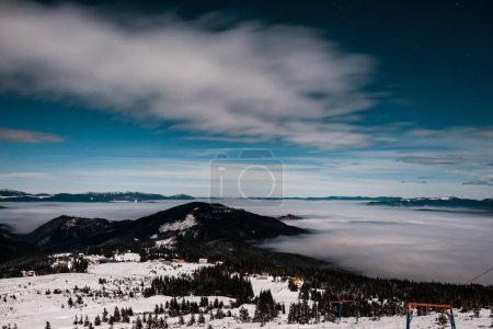 Photo for Scenic view of snowy mountains with pine trees and white fluffy clouds in dark sky in evening - Royalty Free Image