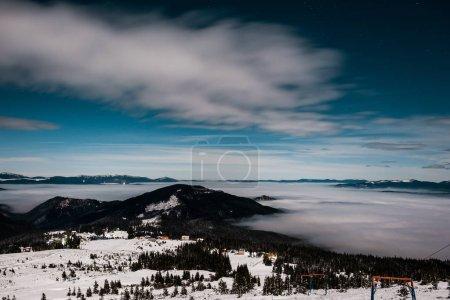 Photo pour Vue panoramique des montagnes enneigées avec des pins et des nuages blancs pelucheux dans le ciel sombre en soirée - image libre de droit