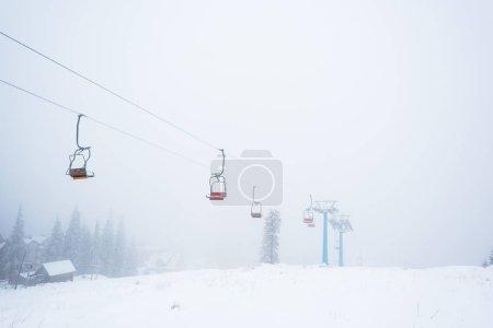 Photo pour Vue panoramique sur la montagne enneigée avec télécabine dans le brouillard - image libre de droit