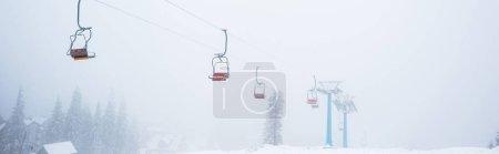 Photo pour Vue panoramique sur la montagne enneigée avec télécabine dans le brouillard, vue panoramique - image libre de droit