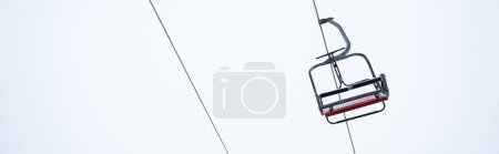 Photo for Seat of gondola lift against pure white sky background, panoramic shot - Royalty Free Image