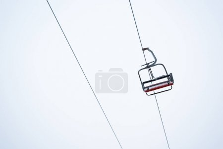 Photo for Seat of gondola lift against pure white sky background - Royalty Free Image