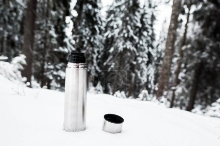 Photo for Vacuum flask with hot drink on hill covered with snow near pine forest - Royalty Free Image