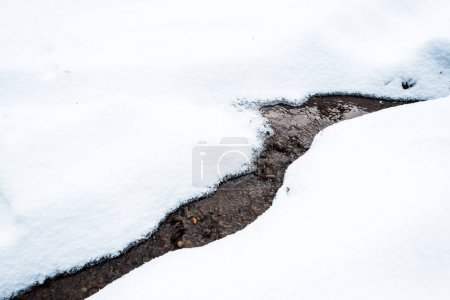 Foto de Torrente montañoso que fluye a través de la nieve blanca - Imagen libre de derechos
