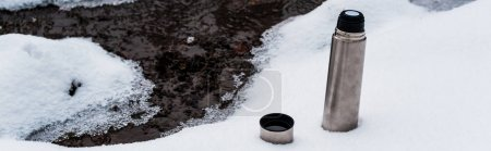 Photo for Vacuum flask on snow near flowing mountain stream, panoramic shot - Royalty Free Image