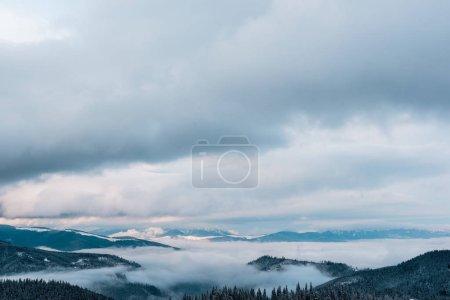 malerischer Blick auf schneebedeckte Berge mit weißen, flauschigen Wolken
