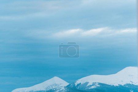 malerischer Blick auf verschneite Berge mit weißem bewölkten Himmel