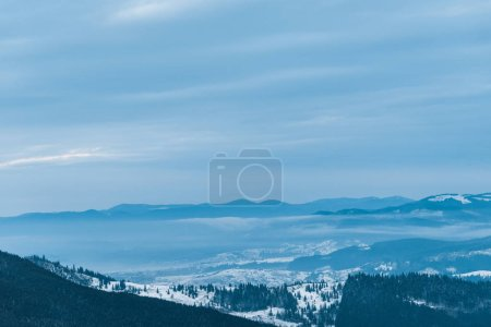 Photo for Scenic view of snowy mountains with pine trees and cloudy sky - Royalty Free Image