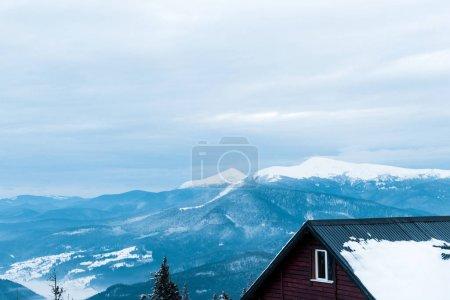 Foto de Vista panorámica de las montañas nevadas con pinos y casa de madera. - Imagen libre de derechos