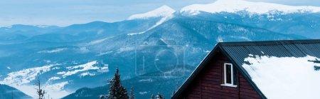 Foto de Vista panorámica de montañas nevadas con pinos y casa de madera, tiro panorámico. - Imagen libre de derechos