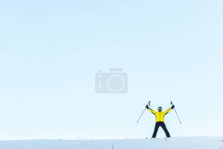 Photo for Skier in helmet holding sticks while standing on snow - Royalty Free Image