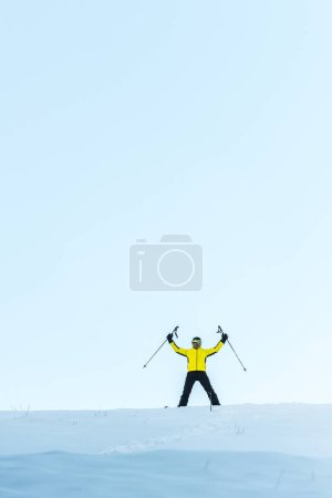 Photo for Skier in helmet holding sticks while standing on snow in mountains - Royalty Free Image