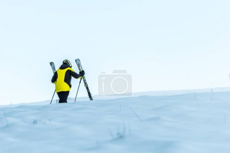 Photo for Skier in helmet holding sticks while walking on white snow - Royalty Free Image