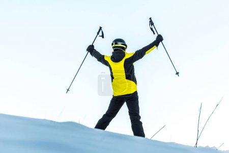 Foto de Vista trasera del esquiador en casco sosteniendo palos mientras está de pie sobre nieve blanca - Imagen libre de derechos
