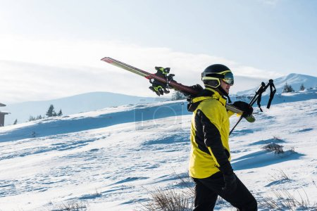 Photo for Side view of skier walking with sticks in mountains - Royalty Free Image