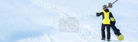 Photo pour Photo panoramique d'un skieur en casque marchant avec des bâtons sur de la neige blanche en montagne - image libre de droit