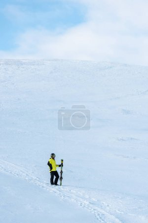Photo for Sportsman in helmet standing with ski sticks on white snow in mountains - Royalty Free Image