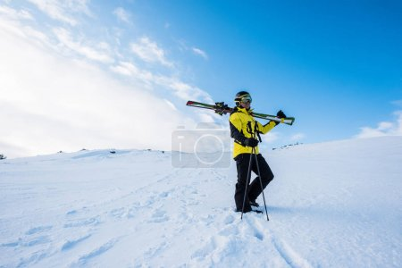 Photo for Sportsman in helmet standing with ski sticks on snow in mountains - Royalty Free Image