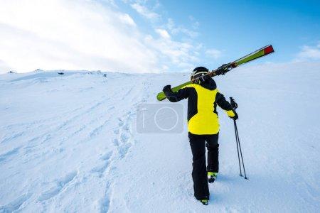 Foto de Vista trasera del esquiador caminando con bastones de esquí en la nieve - Imagen libre de derechos