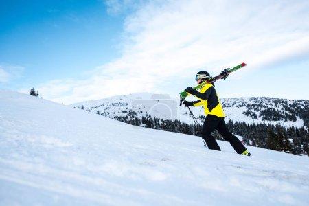 Photo pour Vue latérale d'un skieur marchant avec des bâtons de ski sur la neige - image libre de droit