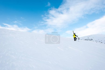 Photo for Skier in helmet walking with ski sticks on slope in wintertime - Royalty Free Image