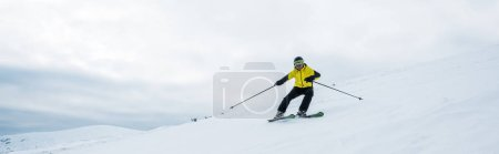 Foto de Plano panorámico del deportista sosteniendo bastones de esquí mientras esquiaba sobre nieve blanca - Imagen libre de derechos