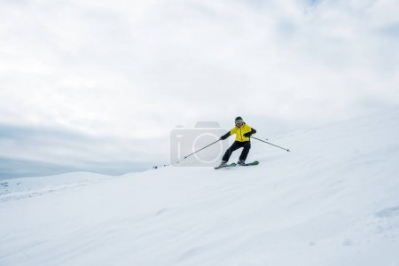 Photo for Sportsman holding ski sticks and skiing on white slope - Royalty Free Image