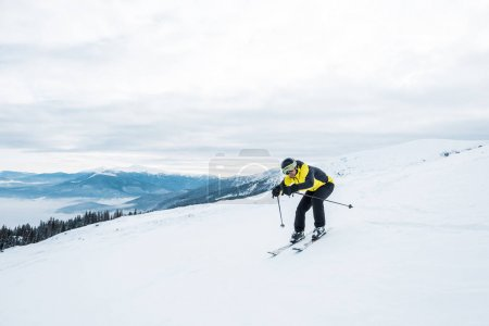 Photo for Sportsman holding ski sticks and skiing on white slope in mountains - Royalty Free Image