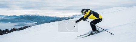 Photo pour Photo panoramique d'un sportif skiant sur une pente montagneuse - image libre de droit