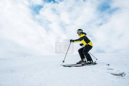 Photo pour Un sportif portant un casque et des lunettes de ski sur la pente - image libre de droit
