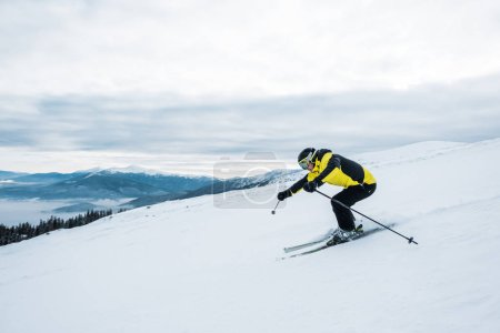 Photo for Athletic man in helmet and goggles skiing on slope - Royalty Free Image